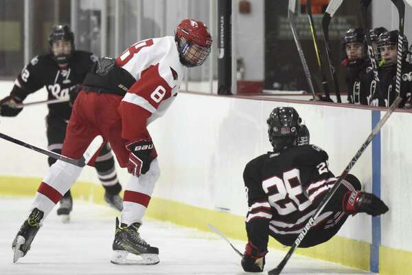 Greenwich's Alex Mozian checks New Canaan's Shane Pickering into the boards on Monday evening at Dorothy Hamill Rink in Greenwich