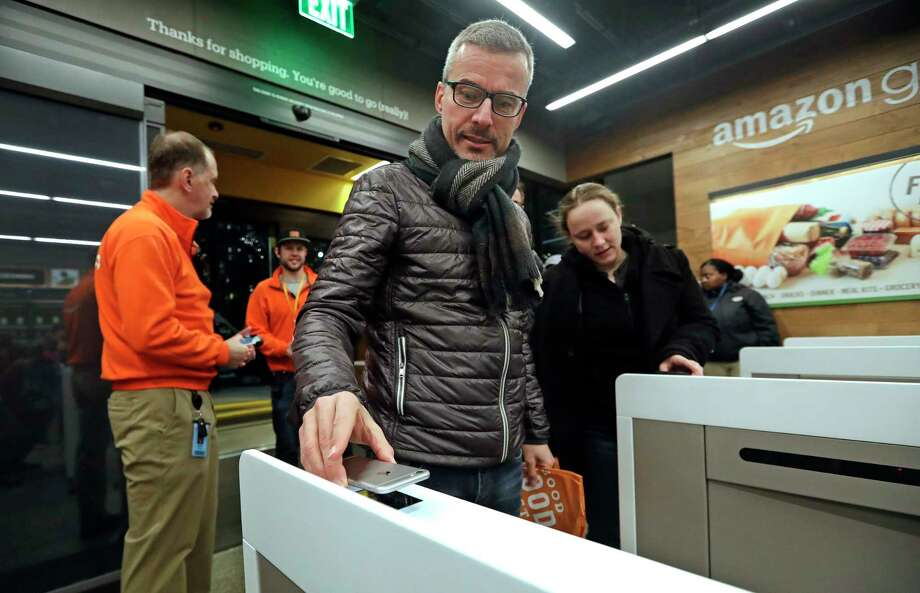 A customer scans his Amazon Go cellphone app at the entrance as he heads into an Amazon Go store, Monday, Jan. 22, 2018, in Seattle. The store, which opened to the public on Monday, allows shoppers to scan their smartphone with the Amazon Go app at a turnstile, pick out the items they want and leave. The online retail giant can tell what people have purchased and automatically charges their Amazon account. (AP Photo/Elaine Thompson) Photo: Elaine Thompson, STF / Copyright 2018 The Associated Press. All rights reserved.