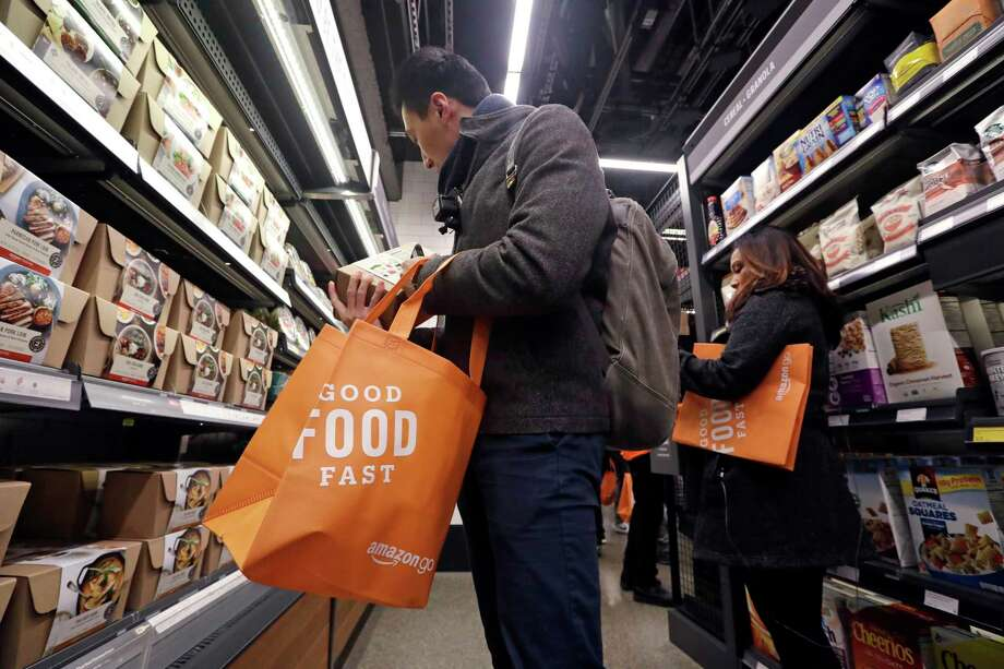 Paul Fan shops at an Amazon Go store in Seattle. Amazon's technology charges customers after they leave. Photo: Elaine Thompson, STF / Copyright 2018 The Associated Press. All rights reserved.