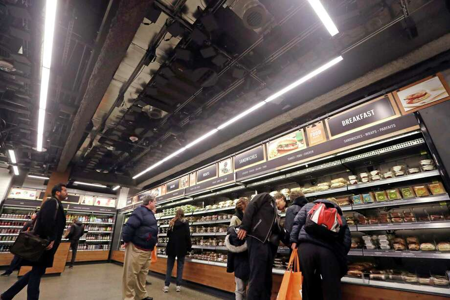 Sensors and cameras, part of a system used to tell what people have purchased, are attached overhead as shoppers walk below, in an Amazon Go store, Monday, Jan. 22, 2018, in Seattle. The artificial intelligence-powered store, which opened to the public Monday, allows shoppers to scan their smartphone with the Amazon Go app at a turnstile, pick out the items they want and leave. The online retail giant can tell what people have purchased and automatically charges their Amazon account. (AP Photo/Elaine Thompson) Photo: Elaine Thompson, STF / Copyright 2018 The Associated Press. All rights reserved.