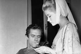 In this Dec. 19, 1960 file photo, actress Dolores Hart lights a cigarette for actor Bradford Dillman, in a break of the shooting the movie, Saint Francis of Assisi, in Rome. Dillman had the starring role of Saint Francis, while Hart played the part of Saint Clare, the nun who founded the order of St. Clare.  Hart walked away from stardom in 1963 to become a nun at an abbey in rural Bethlehem, Conn., which needs millions of dollars in renovations in December 2011to meet safety codes.  (AP Photo/CR, File)