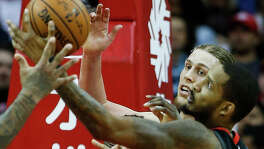 Back from a two-game suspension, the Rockets' Trevor Ariza, right, battles Miami's Kelly Olynyk for a rebound.
