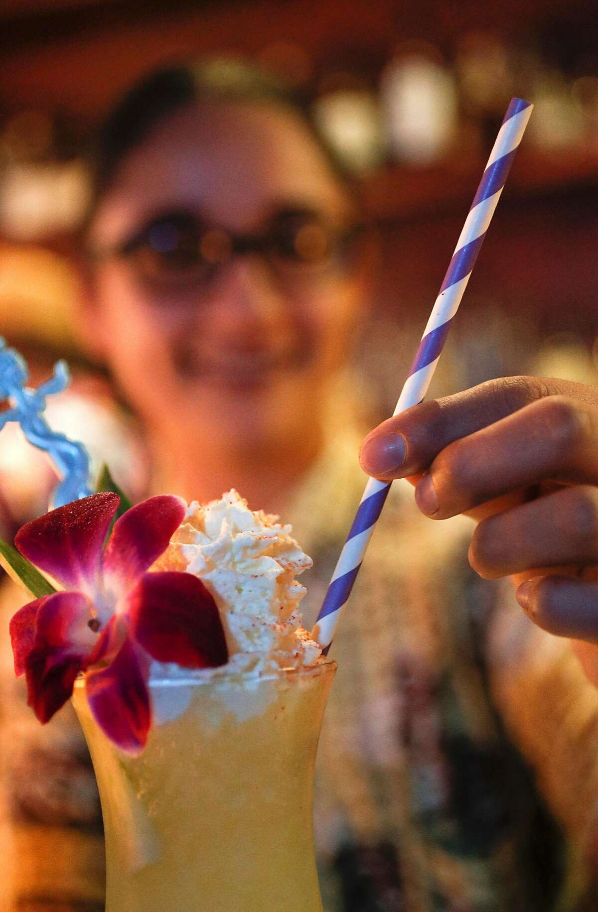 Bartender Maritza Rocha serves an island inspired cocktail along with a paper straw at the Pagan Idol where they have been using paper straws in their drinks for the past one and a half years, as seen on Friday, Jan. 19, 2018 in San Francisco, Calif. There is a bill in California is passed would ban plastic straws at dine-in restaurants unless a customer asks for one.