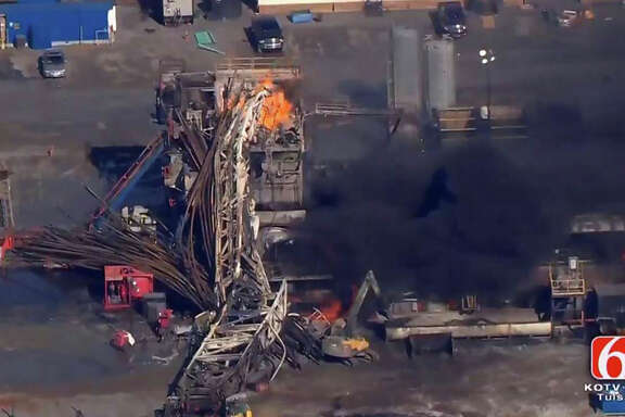 In this photo provided from a frame grab from Tulsa's KOTV/NewsOn6.com, fires burn at an eastern Oklahoma drilling rig near Quinton, Okla., Monday Jan. 22, 2018. Five people are missing after a fiery explosion ripped through a drilling rig, sending plumes of black smoke into the air and leaving a derrick crumpled on the ground, emergency officials said. (Christina Goodvoice, KOTV/NewsOn6.com via AP)