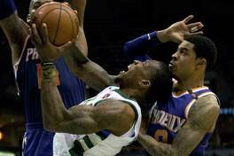 Milwaukee Bucks guard Eric Bledsoe, center, is defended by Phoenix Suns center Greg Monroe, left, and Tyler Ulis, right, during the first half of an NBA basketball game Monday, Jan. 22, 2018, in Milwaukee. (AP Photo/Darren Hauck)