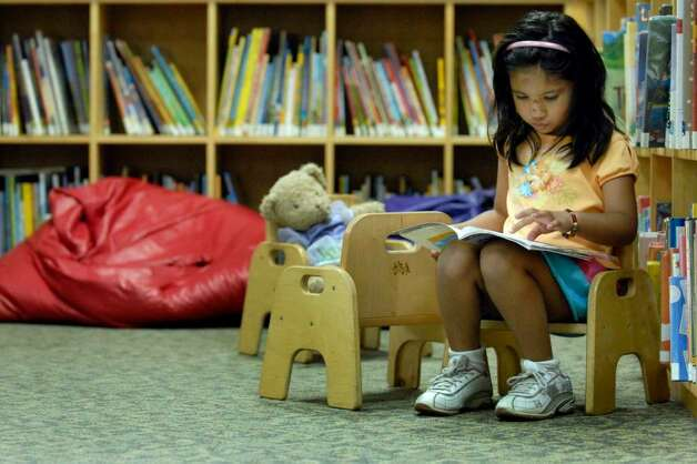 Rubab Khan, 4, reads a book in the childrens section at the Albany Public Library last week. ( Michael P. Farrell / Times Union ) Photo: MICHAEL P. FARRELL / 00004744A