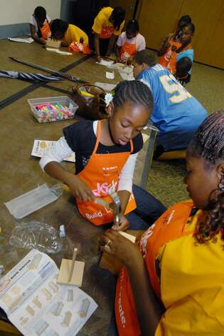 Netavia Walters, 8, left, works on a bird house with Jahsylvia Holland at the Albany Public Library Thursday. ( Michael P. Farrell / Times Union ) Photo: MICHAEL P. FARRELL / 00004744A