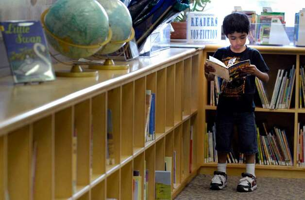 Haider Khan, 6, reads a book in the childrens section at the Albany Public Library last week. ( Michael P. Farrell / Times Union ) Photo: MICHAEL P. FARRELL / 00004744A