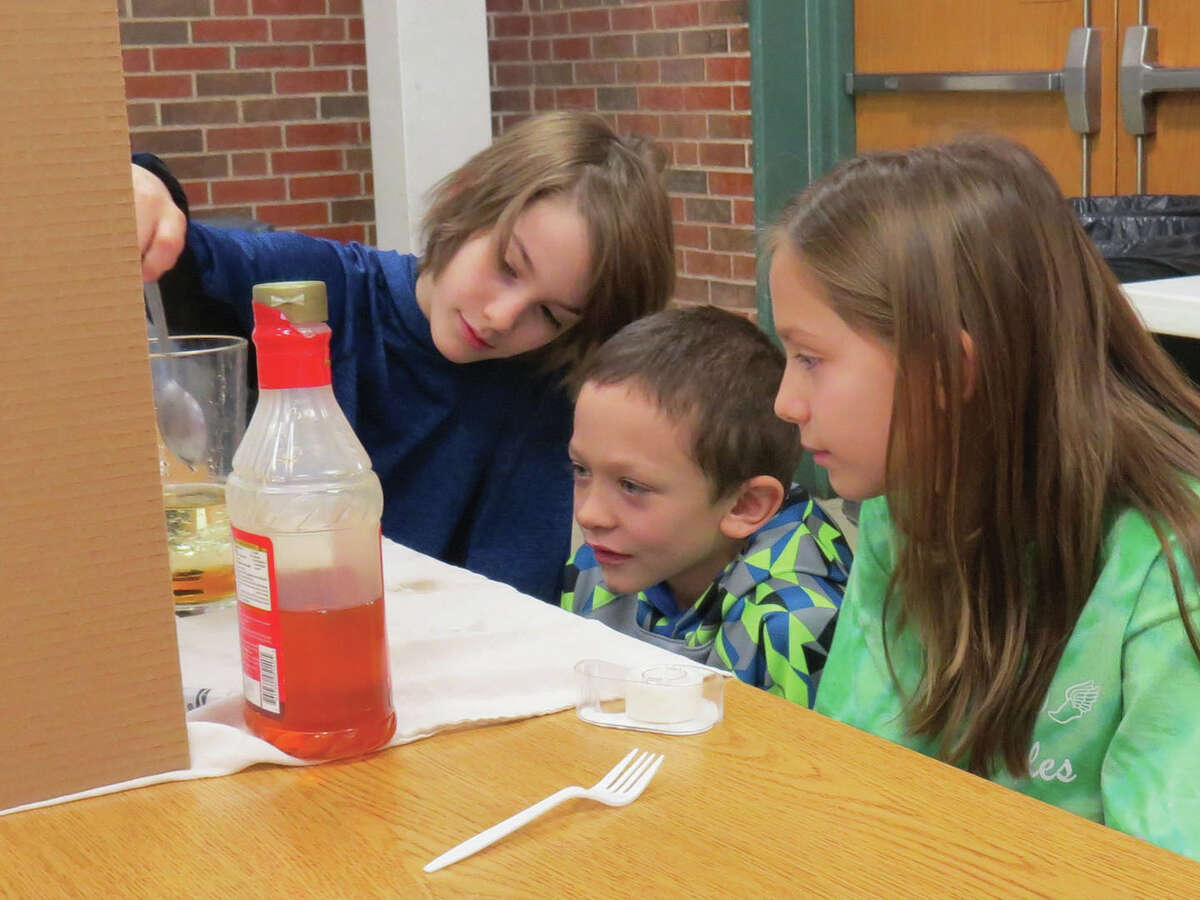 Erik N., left, and Ellie N., right, demonstrate their experiment to Lucas A., center, Friday during Trinity Lutheran School's Science Fair, which was presented by the fifth grade.
