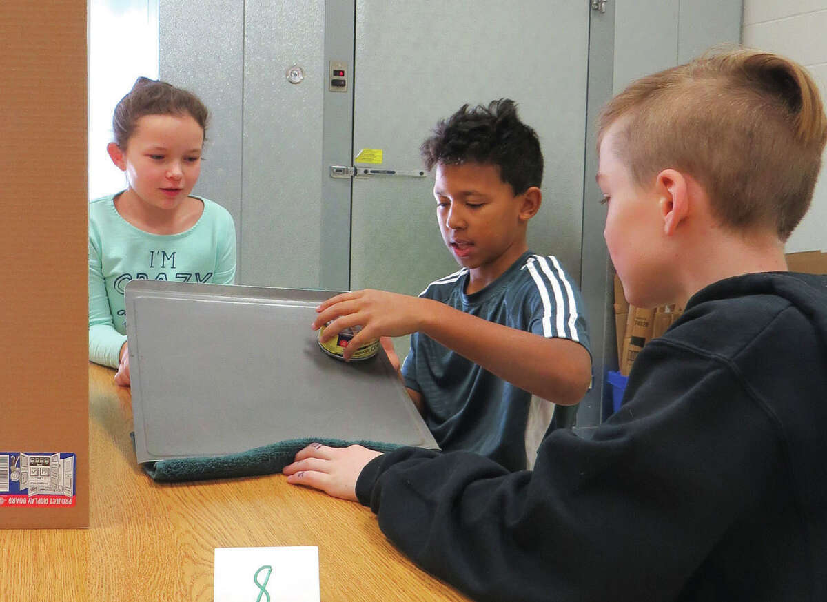 Thijson, center and Jacob D. right, demonstrate their experiment to Lilly L. during the fifth-grade Science Fair at Trinity Lutheran School. Students up to fourth grade were invited to the gymnasium to view the fifth graders' work.