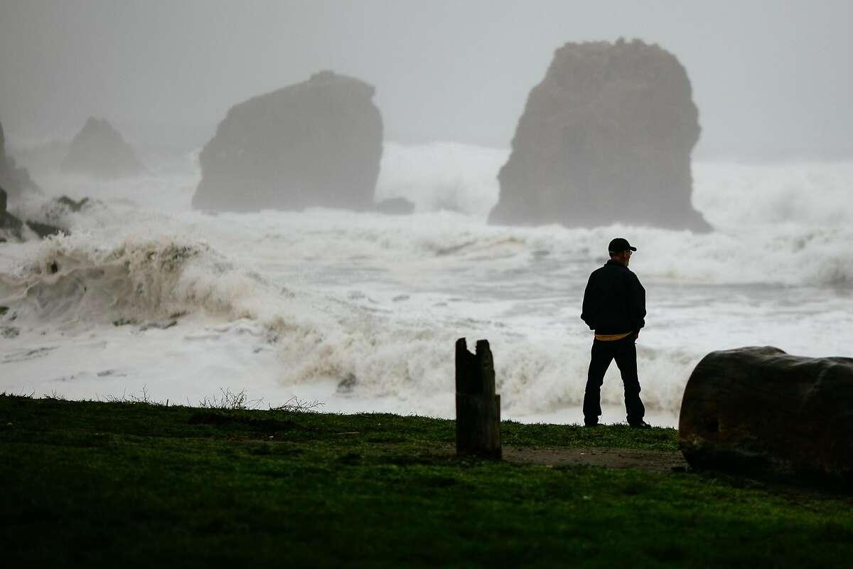 An onlooker watches as Ocean swell crash along the shoreline on Rockaway Beach in Pacifica, Calif. Thursday, Jan. 18, 2018.