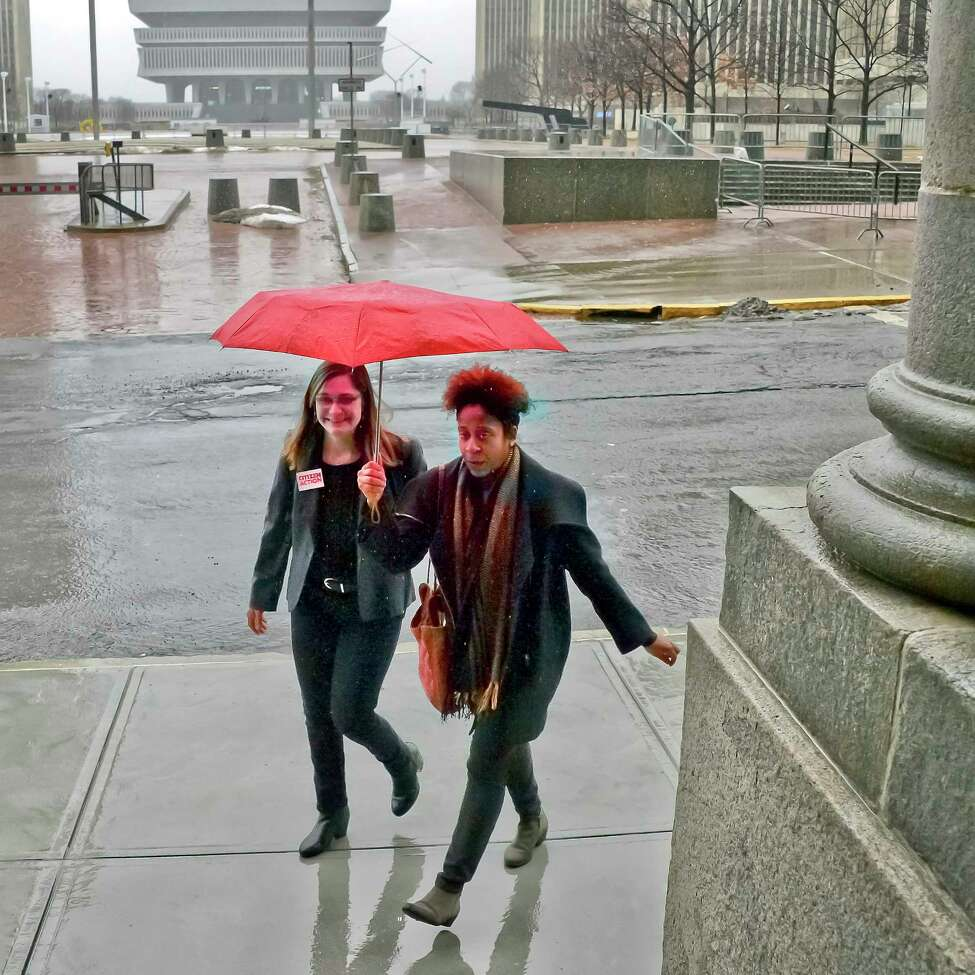Jess Wisneski, left and Janel Quarless share an umbrella on their way to a voting rights rally at the Capitol Tuesday Jan. 23, 2018 in Albany, NY. (John Carl D'Annibale/Times Union)