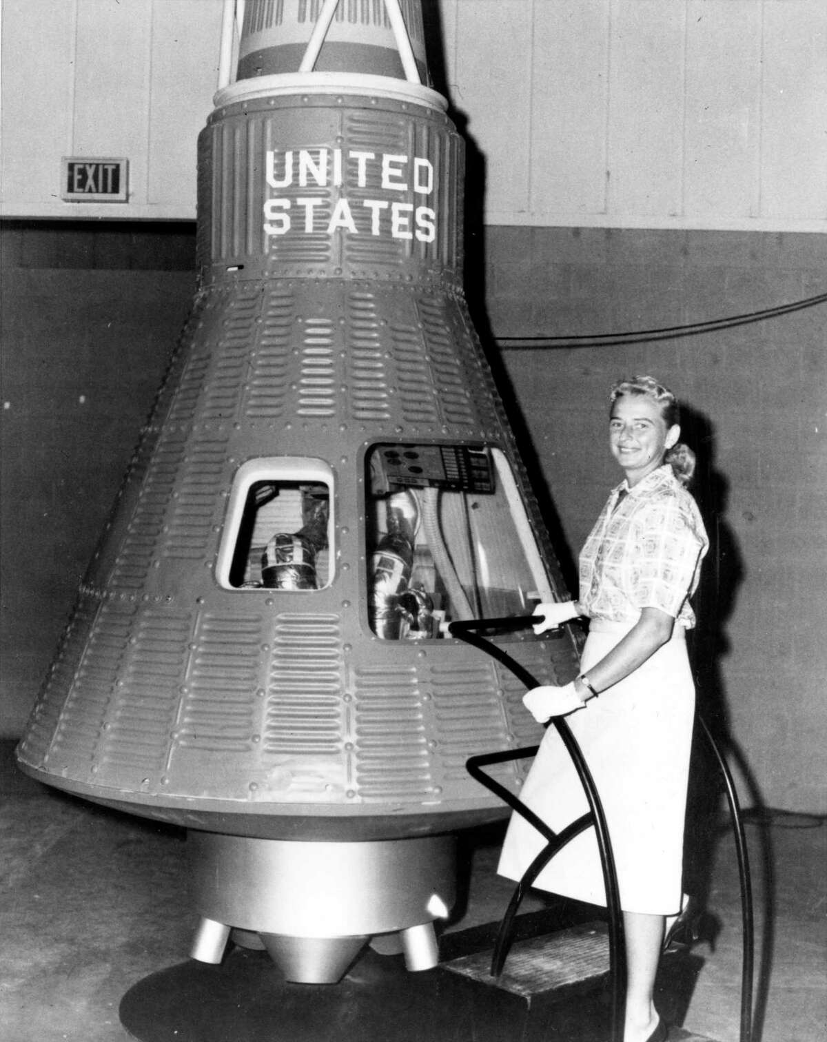 Jerrie Cobb poses next to a Mercury spaceship capsule. Cobb, along with 24 other women, underwent physical tests similar to those taken by the Mercury astronauts with the belief that she might become an astronaut trainee. All the women who participated in the program, known as First Lady Astronaut Trainees (FLAT), were skilled pilots. But the program was not sanctioned by NASA and was shuttered.