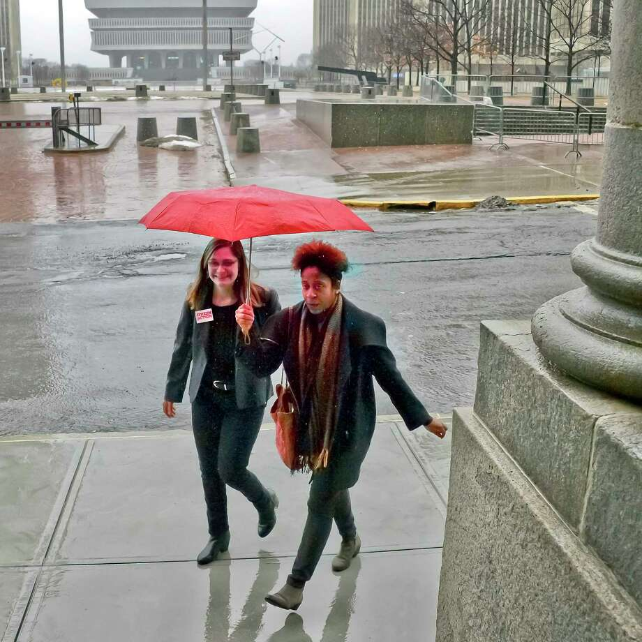 Jess Wisneski, left and Janel Quarless share an umbrella on their way to a voting rights rally at the Capitol Tuesday Jan. 23, 2018 in Albany, NY.  (John Carl D'Annibale/Times Union) Photo: John Carl D'Annibale, Albany Times Union