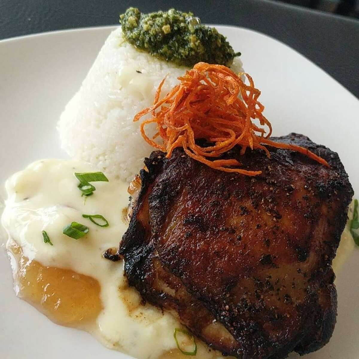 Pepper-crusted chicken thigh with sushi rice, garden pesto and coconut rum sauce at Sylver Spoon, a new restaurant and theater at 6700 N. Interstate 35 in New Braunfels.
