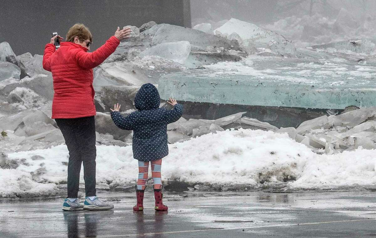 Ice on the Mohawk River mounts up in the parking area of Jumping Jacks restaurant as Barbara Phillips demonstrates the size of the chunks to her granddaughter Vietta Phillips, 31/2 from Clifton Park Tuesday, Jan 23, 2018 in Scotia, N.Y. (Skip Dickstein/Times Union)