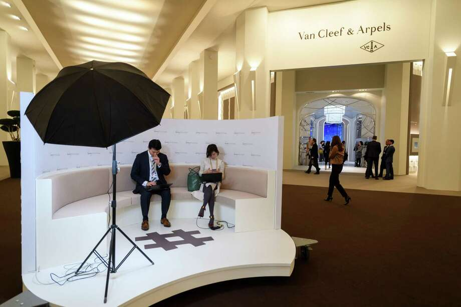Visitors sit next to the stand of the French jewelry, watch, and perfume company Van Cleef & Arpels, owned by Switzerland-based luxury goods holding company Richemont, on the opening day of the 28th International Fine Watchmaking Exhibition SIHH, on January 15, 2018 in Geneva. Photo: FABRICE COFFRINI /AFP /Getty Images / AFP or licensors