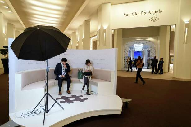 Visitors sit next to the stand of the French jewelry, watch, and perfume company Van Cleef & Arpels, owned by Switzerland-based luxury goods holding company Richemont, on the opening day of the 28th International Fine Watchmaking Exhibition SIHH, on January 15, 2018 in Geneva.