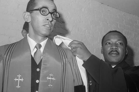 "(Original Caption) 3/25/1968-New York, NY: Civil rights leader Dr. Martin Luther King (right) installs the Rev. Wyatt T. Walker as pastor of the New Canaan Baptist Church here March 24. As the ceremony was going on, former Congressman Adam Clayton Powell, just back from the Bahamas, was leading a march through Harlem. As he passed the New Canaan Church, Powell shouted ""Judas"" but it was not clear whether he referred to Walker or to King."