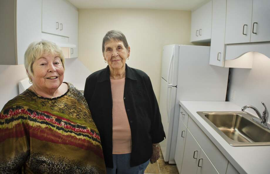 Washington Woods residents Sue LaMee, 64, left, and Jean Keppel, 87, right, pose for a photo inside the kitchen of one of the newly renovated apartments at Washington Woods on Friday, Jan. 19, 2018. (Katy Kildee/kkildee@mdn.net) Photo: (Katy Kildee/kkildee@mdn.net)
