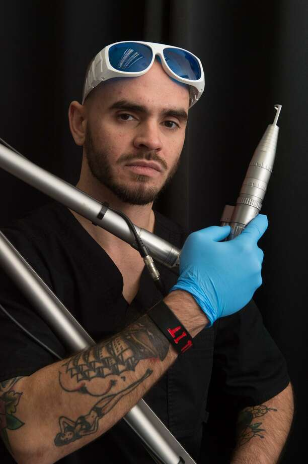 Zack Wells, a certified laser specialists at the MEDermis Laser Clinic, poses with one of the lasers he uses to remove no-longer-loved tattoos. Photo: Robin Jerstad /For The Express-News / ROBERT JERSTAD