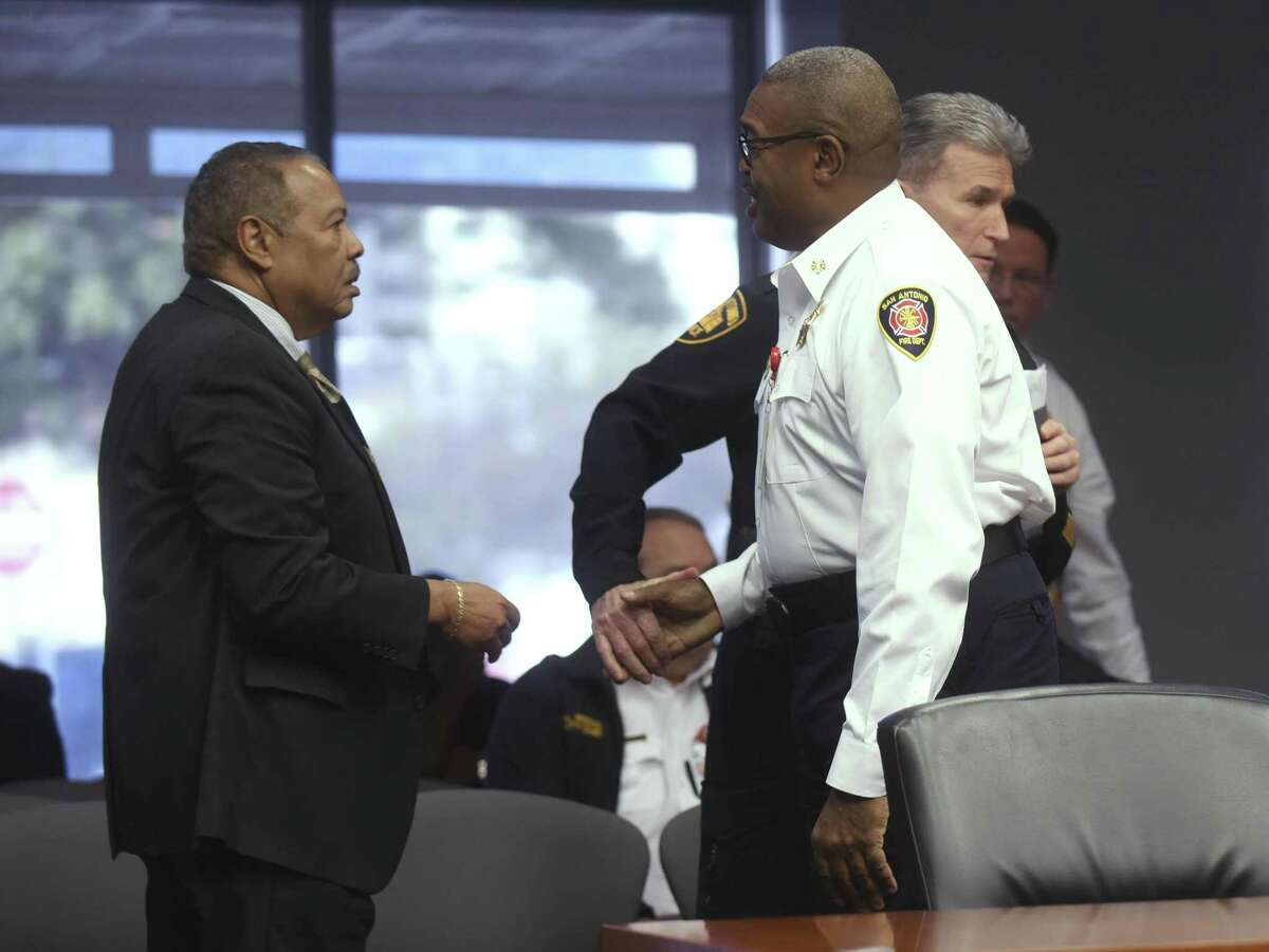 San Antonio Police Chief William McManus (right) shakes hands with Fire Chief Charles Hood after speaking to the City Council's public safety subcommittee Tuesday. Robert Stewart of Bobcat Training and Consulting stands at the left.