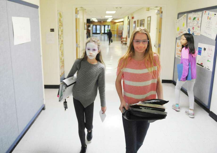 """Seventh-graders Emily Phillipps, left, and Samantha Johnson walk down the hallways as a bunny and a pig after getting a special effects makeup makeover at Eastern Middle School in the Riverside section of Greenwich, Conn. Tuesday, Jan. 23, 2018. Makeup artist Tyler Green, a finalist on Syfy's """"Face Off"""" SFX makeup reality show, gave demos transforming students into whimsical characters with the application of facial prosthetics and makeup. Photo: Tyler Sizemore / Hearst Connecticut Media / Greenwich Time"""
