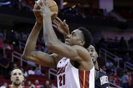 Miami Heat center Hassan Whiteside (21) shoots past Houston Rockets guard Chris Paul (3) as forward Ryan Anderson (33) looks on during the first half of an NBA basketball game Monday, Jan. 22, 2018, in Houston. (AP Photo/Michael Wyke)