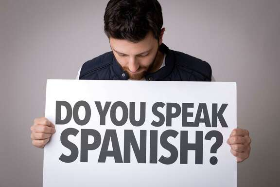 "A man holds a sign asking ""Do you Speak Spanish?"""