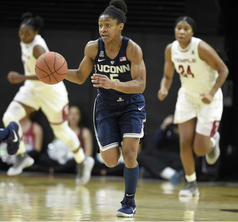 UConn guard Crystal Dangerfield pushes the ball up court against Temple during the first half on Sunday in Philadelphia. Photo: John Woike / Tribune News Service / Hartford Courant