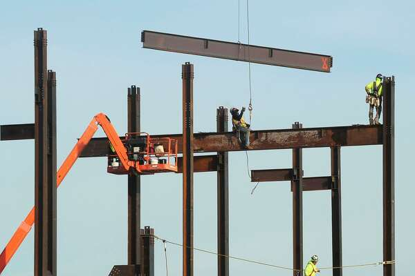 Steel workers move I-beams into place as the Sono Collection development begins to grow vertically.