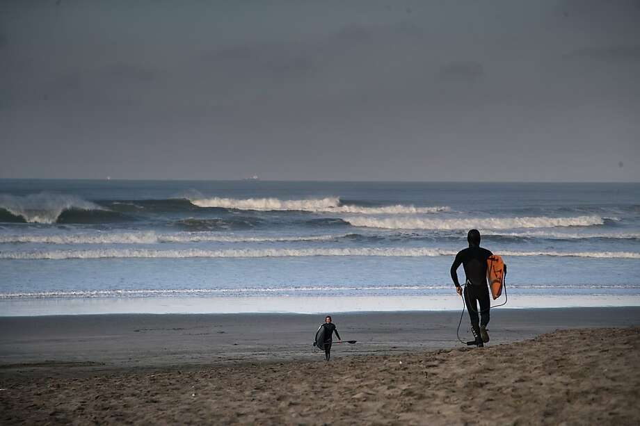 Lewis Samuels, who missed the alert about a possible tsunami and the later cancellation, heads out to surf at Ocean Beach in San Francisco Tuesday. The alert didn't cause too much of a stir in San Francisco. Photo: Paul Kuroda, Special To The Chronicle