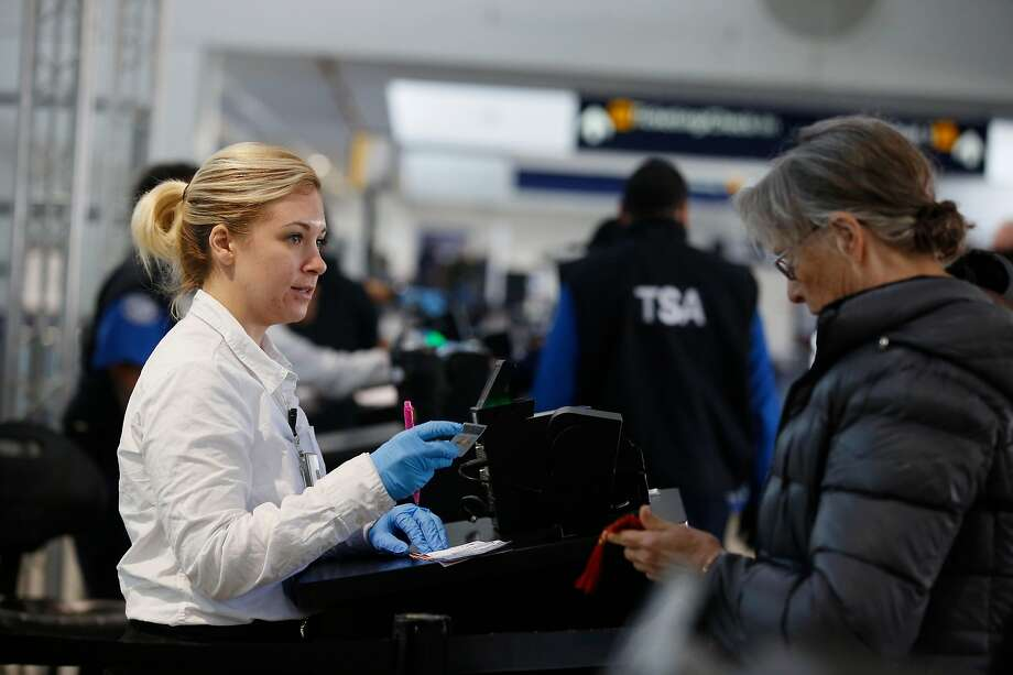 A security agent checks a traveler's driver's license at Oakland International Airport. Starting in October 2020, Real ID licenses or passports will be needed to board a plane in the U.S. Photo: Lea Suzuki, The Chronicle
