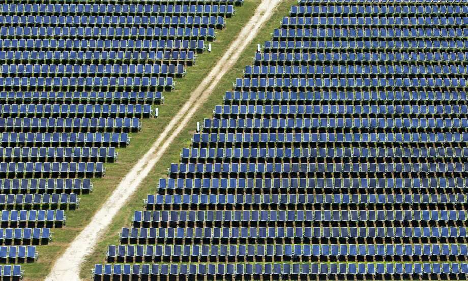 Solar panels line a maintenance road at OCI Solar Power's Alamo 1 solar plant on San Antonio's south side. The company recently announced that it has purchased a 50 megawatt solar farm under development in West Texas for an undisclosed amount of money. Photo: William Luther /San Antonio Express-News / © 2017 San Antonio Express-News