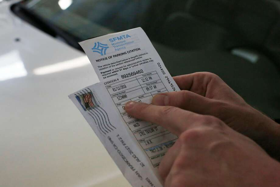 Kristap Baltin, who filed a police report after his car was stolen on January 7, 2018, holds a parking ticket issued to his car on January 11, 2018 which he found in his back seat as he picks his car up at San Francisco Auto Works for repairs resulting from the theft, on Monday, January 22, 2018 in San Francisco, Calif.  Baltin, who filed a police report after his car was stolen on January 7, 2018, received two parking tickets on his car during the period it was stolen. Photo: Lea Suzuki, The Chronicle
