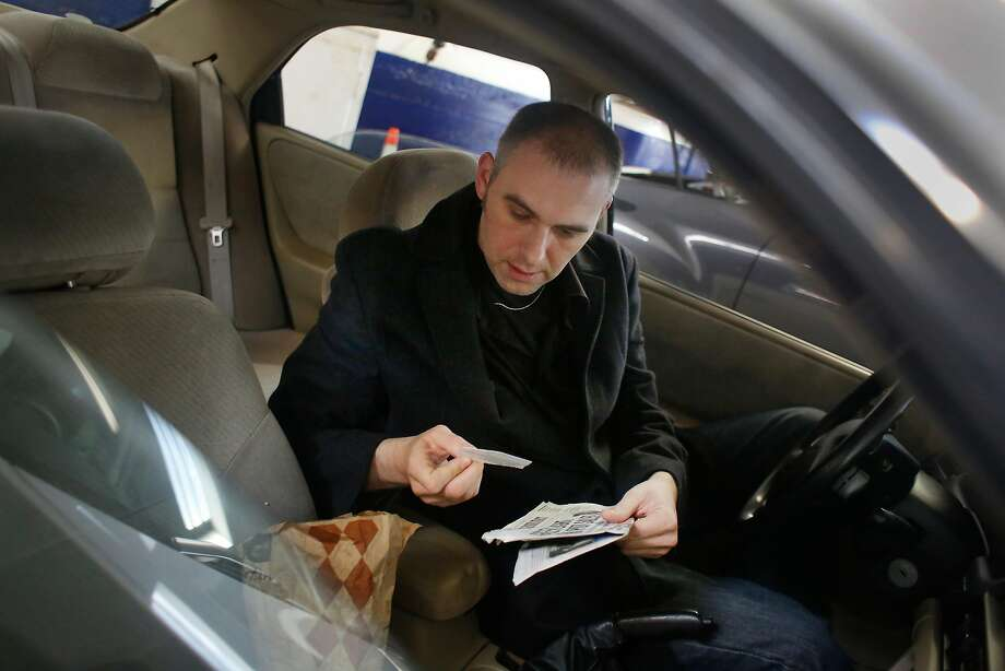 Kristap Baltin, whose car was stolen Jan. 7 — and ticketed — looks over items he had left inside that were not touched. Photo: Lea Suzuki, The Chronicle