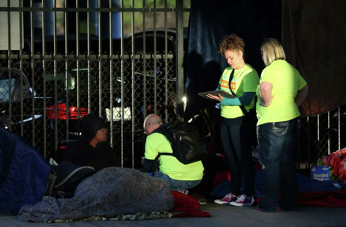 Preston Witt, center to right, Meg Pohodich, and Amy Jo Davison talk with a woman who is currently homeless near Pierce Street Tuesday, Jan. 23, 2018, in Houston. Volunteers with The Coalition for the Homeless conducted the annual count and survey of the homeless population. ( Godofredo A. Vasquez / Houston Chronicle )