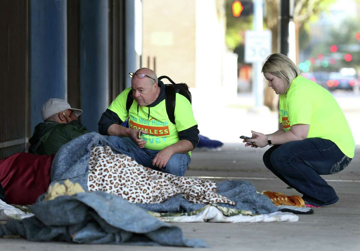 Preston Witt, center, and Amy Jo Davison, right, conduct a survey with a man who is currently homeless under the Gulf Freeway near Pierce Street Tuesday, Jan. 23, 2018, in Houston. Volunteers with The Coalition for the Homeless conducted the annual count and survey of the homeless population. ( Godofredo A. Vasquez / Houston Chronicle )