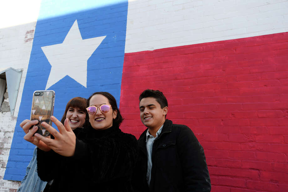 Kat Werner, Julia Rodriguez and Justin Norris take a group photo in front of a Texas flag mural in Port Neches.  Photo taken Wednesday 1/17/18 Ryan Pelham/The Enterprise Photo: Ryan Pelham / ©2017 The Beaumont Enterprise/Ryan Pelham