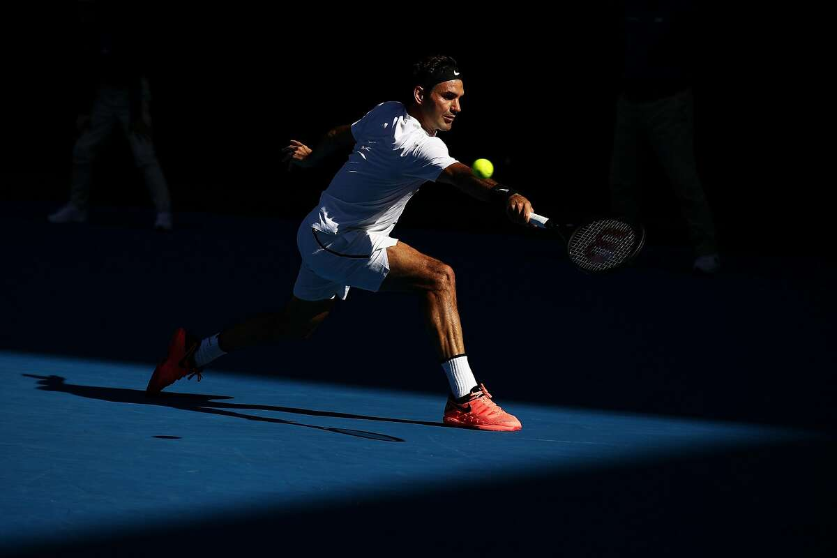 MELBOURNE, AUSTRALIA - JANUARY 22: Roger Federer of Switzerland plays a backhand in his fourth round match against Marton Fucsovics of Hungary on day eight of the 2018 Australian Open at Melbourne Park on January 22, 2018 in Melbourne, Australia. (Photo by Cameron Spencer/Getty Images)