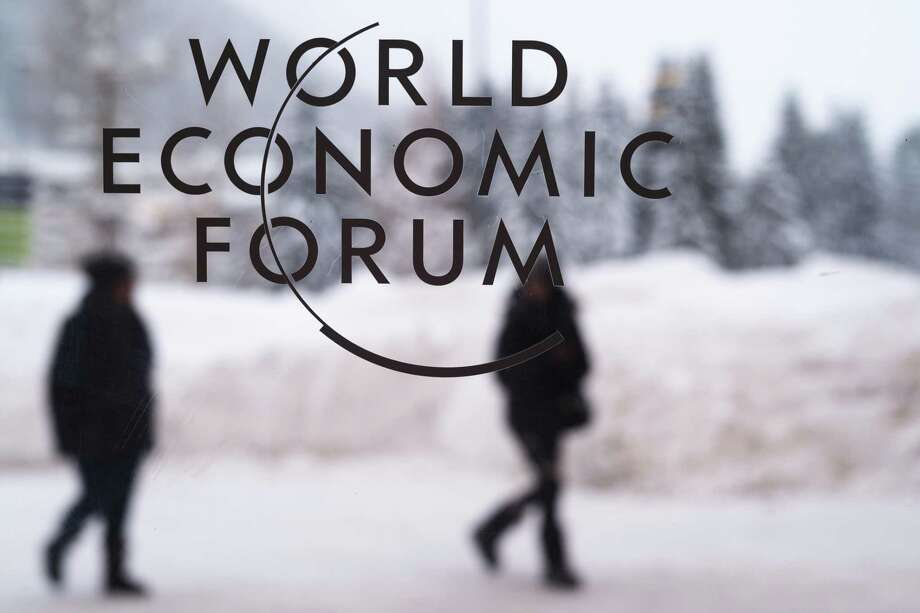 Two persons walk behind the logo of the World Economic Forum at the meeting's conference center in Davos, Switzerland, Sunday, Jan. 21, 2018. One question looms as President Donald Trump packs his bags and heads for the mountains of Switzerland later this week: How will the diet Coke-loving nationalist fit in with the champagne-swilling globalists hell encounter at the World Economic Forum in Davos? Photo: Markus Schreiber /Associated Press / Markus Schreiber
