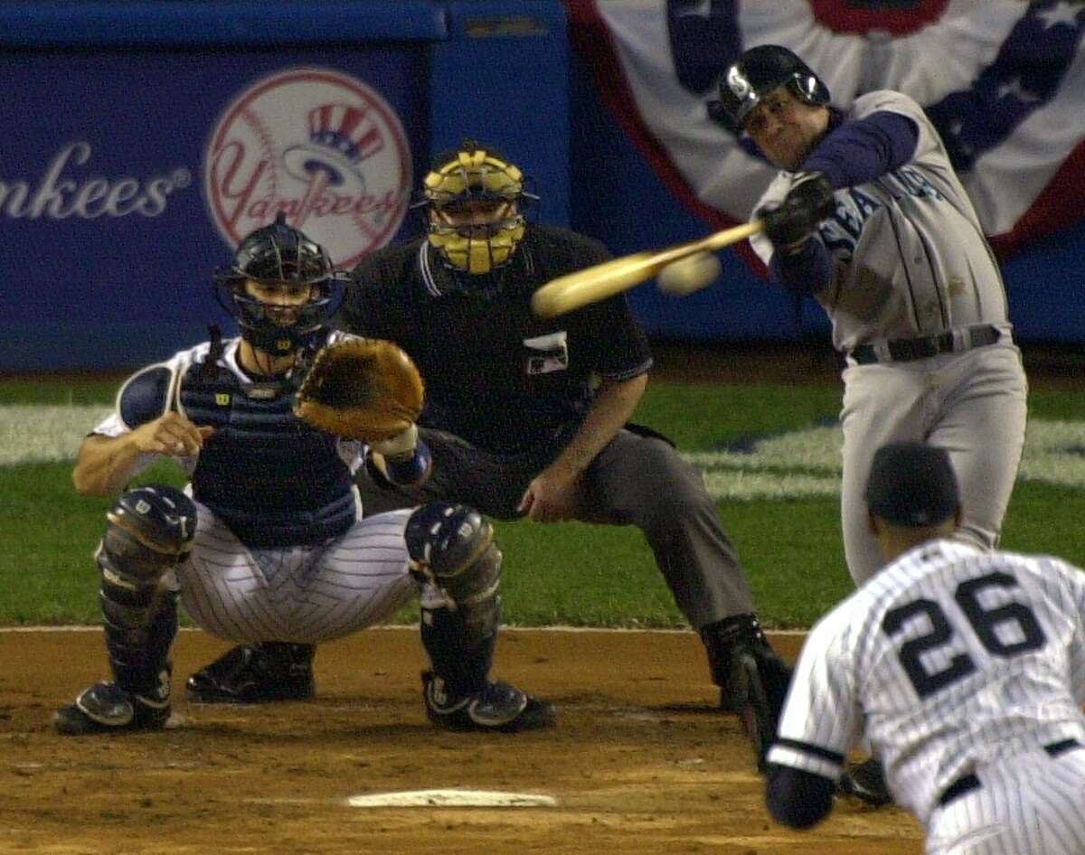 Seattle Mariners' Edgar Martinez hits an RBI double during the first inning of Game 6 of the American League Championship Series against the New York Yankees Tuesday, Oct. 17, 2000, in New York. Yankees catcher Jorge Posada is at left, home plate umpire John Hirschbeck is second from left and Yankees pitcher Orlando Hernandez (26) is at right. (AP Photo/Bill Kostroun)