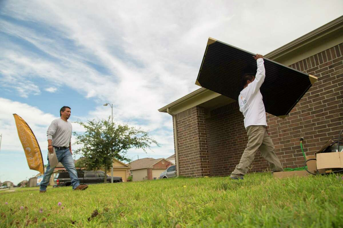 Workers from Alba Solar Energy prepare to install solar panels