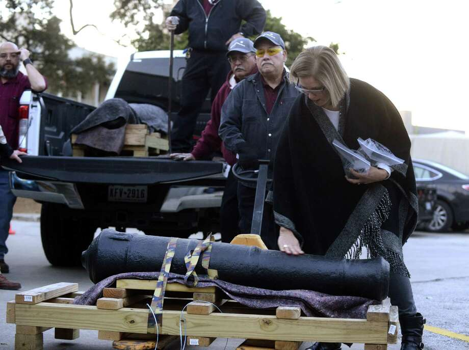 Alamo conservator Pam Rosser examines the Spanish cannon, one of two historic cannons used in the 1836 Battle of the Alamo, upon its return Tuesday from the Texas A&M Conservation Research Lab in College Station. Photo: Billy Calzada /San Antonio Express-News / San Antonio Express-News