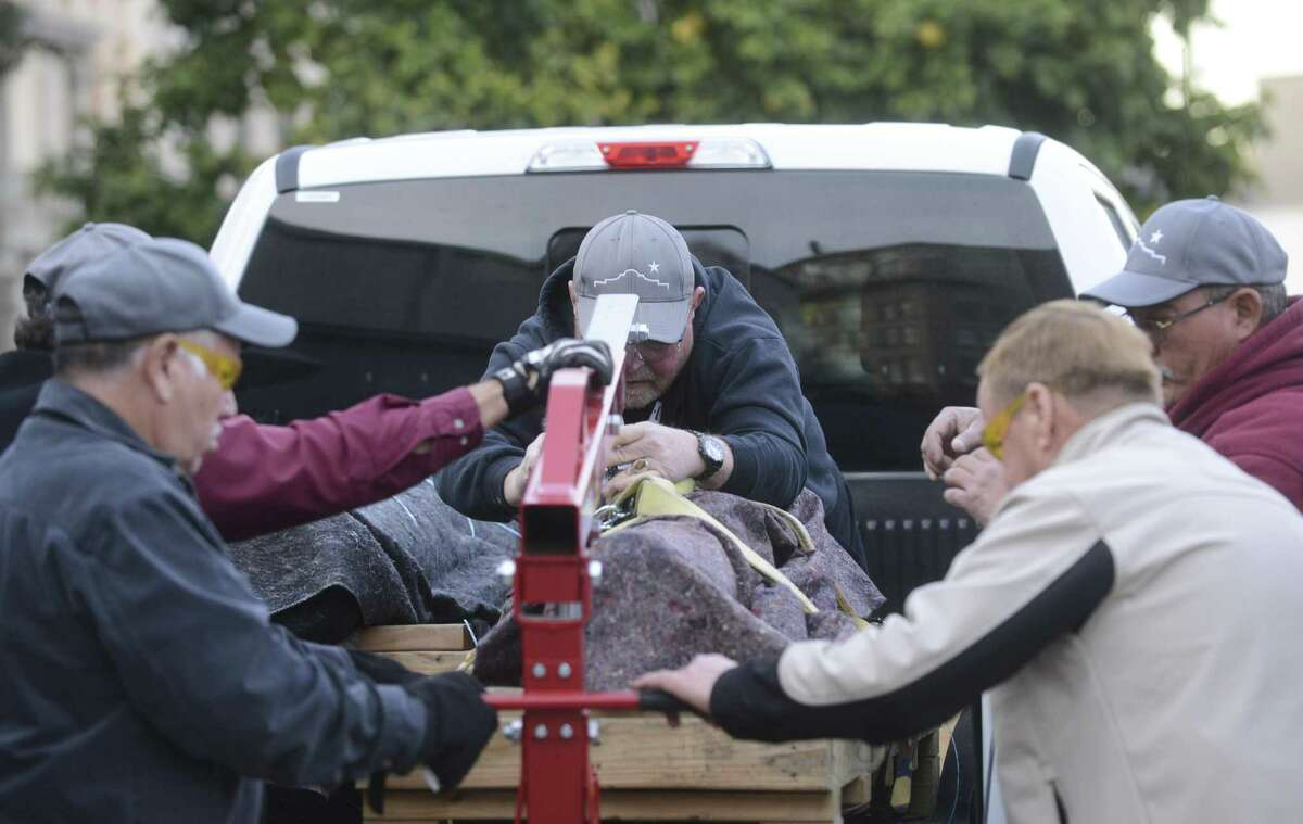 Workers attach a hoist to lift one of two historic Alamo cannons from a pickup truck after they were returned to the Alamo on Tuesday by the Texas A&M Conservation Research Lab in College Station, where they were restored.