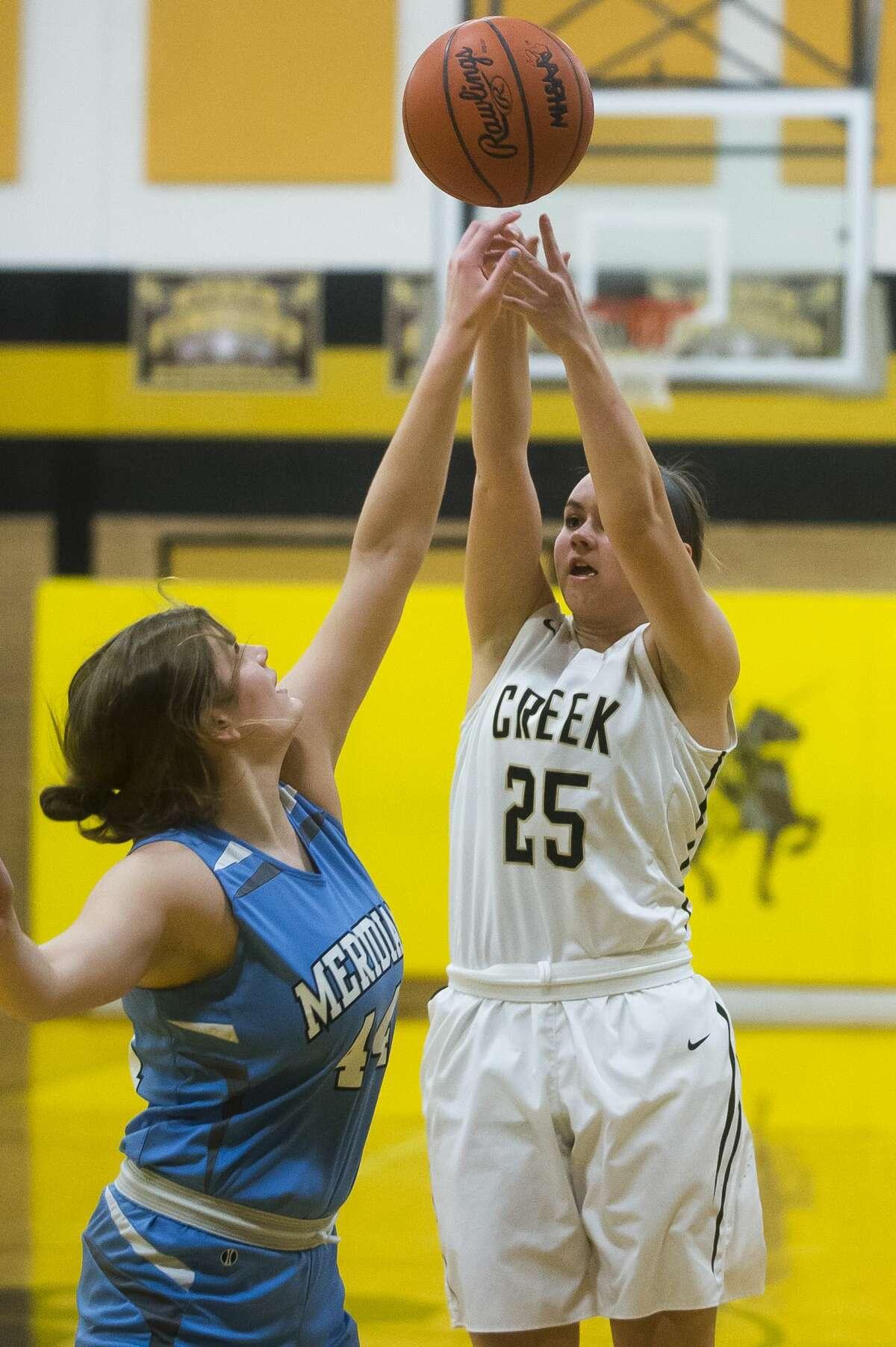 Bullock Creek senior Reegan Carey takes a shot as Meridian junior Baleigh Hill guards her during their game on Tuesday, Jan. 23, 2018 at Bullock Creek High School. Bullock Creek won 42-33. (Katy Kildee/kkildee@mdn.net)