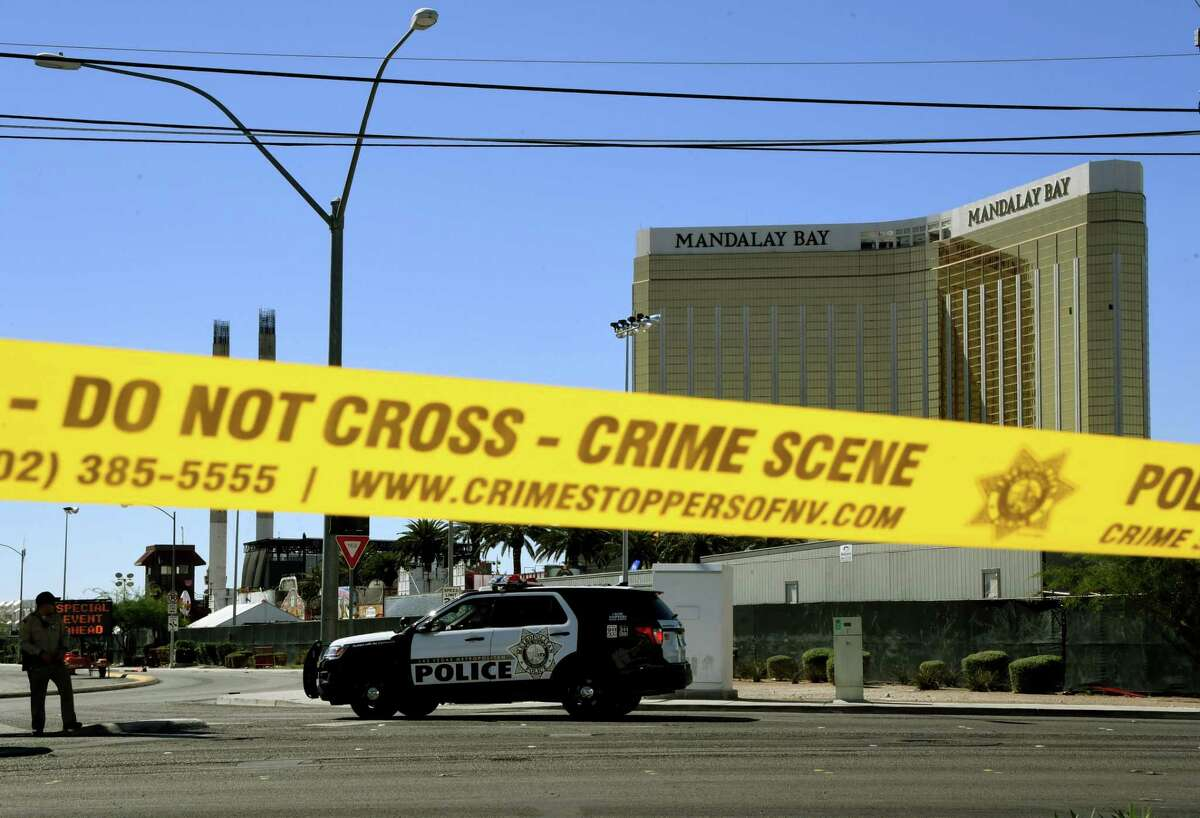 Crime scene tape surrounds the Mandalay Hotel (background with shooters window damage top right) after a gunman killed at least 58 people and wounded more than 500 others when he opened fire on a country music concert in Las Vegas, Nevada on October 2, 2017. Police said the gunman, a 64-year-old local resident named as Stephen Paddock, had been killed after a SWAT team responded to reports of multiple gunfire from the 32nd floor of the Mandalay Bay, a hotel-casino next to the concert venue. / AFP PHOTO / Mark RALSTONMARK RALSTON/AFP/Getty Images