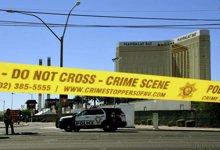 Crime scene tape surrounds the Mandalay Hotel (background with shooters window damage top right) after a gunman killed at least 58 people and wounded more than 500 others when he opened fire on a country music concert in Las Vegas, Nevada on October 2, 2017.  Police said the gunman, a 64-year-old local resident named as Stephen Paddock, had been killed after a SWAT team responded to reports of multiple gunfire from the 32nd floor of the Mandalay Bay, a hotel-casino next to the concert venue. / AFP PHOTO / Mark RALSTONMARK RALSTON/AFP/Getty Images Photo: MARK RALSTON / AFP or licensors
