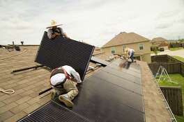 Workers install solar panels on a home in Katy. Rooftop systems are gaining traction in Texas.