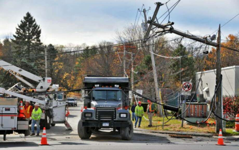 Crews at the scene of a dump truck accident on Route 20, near Rt. 155, in Guilderland that caused damage to several telephone poles Wednesday morning. ( John  Carl  D'Annibale / Times Union)